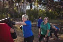 Encajonamiento practicante de la mujer en el campo de bota Foto de archivo