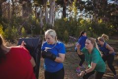 Encajonamiento practicante de la mujer en el campo de bota Imagenes de archivo