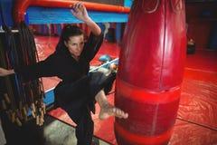 Encajonamiento practicante del jugador femenino del karate con el saco de arena Imagenes de archivo
