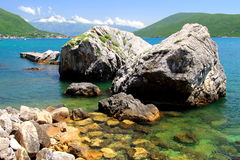 Encalhe com as rochas bonitas, pitorescas no mar e as montanhas na distância Fotos de Stock Royalty Free