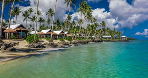Encalhe com com as palmeiras e as casas de campo do coco na ilha de Samoa