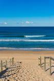 Encalhe a entrada com trilhos e os surfistas de madeira na distância Fotos de Stock Royalty Free