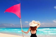 Encalhe a mulher traseira que prende o pólo de bandeira vermelho da praia Imagem de Stock Royalty Free