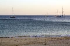 Encalhe no crepúsculo com os veleiros no mar foto de stock