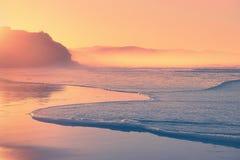 Encalhe no por do sol com espuma da onda na costa Fotos de Stock