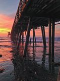 Encalhe o cais no por do sol colorido com reflexões na água Imagem de Stock
