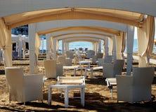 Encalhe o miradouro com mobília da praia, uma atrás da outro ao mar Fotos de Stock Royalty Free