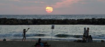 Encalhe os frequentadores silouhetted no por do sol em Tel Aviv, Israel Foto de Stock