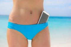 Encalhe a parte inferior de biquini da mulher - conceito do app do smartphone Fotografia de Stock Royalty Free