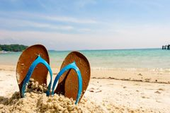 Encalhe sandálias no mar arenoso, ícone do curso das férias foto de stock