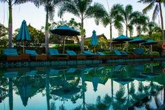 Encalhe sunbeds perto da piscina no recurso tropical com as palmas durante o por do sol, Gili Trawangan, Lombok, Indonésia foto de stock royalty free