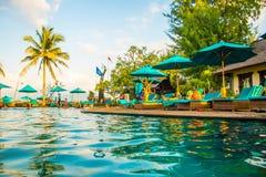 Encalhe sunbeds perto da piscina no recurso tropical com as palmas durante o por do sol, Gili Trawangan, Lombok, Indonésia foto de stock