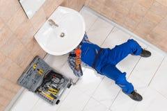 Encanador Lying On Floor que repara o dissipador no banheiro fotos de stock