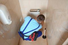 Encanador profissional no tanque de reparação uniforme do toalete Imagens de Stock