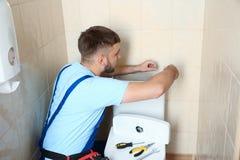 Encanador profissional no toalete de reparação uniforme Imagem de Stock