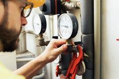 Encanador que instala o medidor da pressão para o sistema de aquecimento fotos de stock