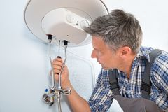 Encanador que repara o aquecedor de água fotografia de stock