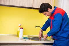 Encanador que repara a torneira na cozinha imagem de stock