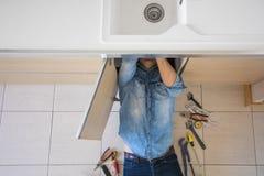 Encanador que trabalha com o encanamento quebrado e escapando da cozinha imagem de stock