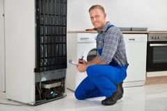 Encanador Writing On Clipboard em Front Of Refrigerator Fotografia de Stock