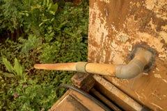 Encanamento plástico da água da válvula velha suja do PVC - textura mofado da parede do vintage Plantas verdes Jardim do campo imagens de stock royalty free