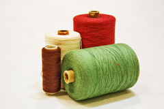 Encanilla los hilos multicolores para coser en un fondo blanco Imágenes de archivo libres de regalías