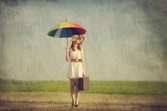 Encantadora del pelirrojo con el paraguas y la maleta en el país de la primavera Imagenes de archivo