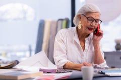 Encantando o chefe de envelhecimento bem arrumado que fala no telefone no escritório imagem de stock royalty free