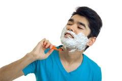 Encantando, o indivíduo encantador inclinou fechado principal seus olhos e barbeia sua máquina da barba imagens de stock