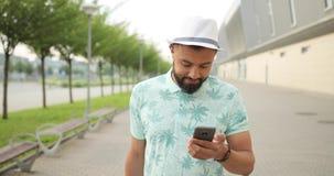 Encantar al hombre bastante africano en el sombrero blanco es de charla y de ojeada en el teléfono móvil Él está mirando la cámar almacen de video