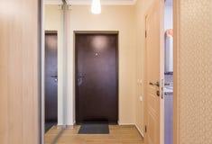 Encante el vestíbulo, la puerta de entrada, guardarropas incorporados y una puerta abierta al cuarto de baño Foto de archivo libre de regalías
