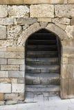 Encante la entrada en una pared de piedra antigua con las escaleras que llevan Imagenes de archivo
