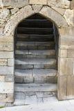 Encante la entrada en una pared de piedra antigua con las escaleras que llevan Imagen de archivo libre de regalías
