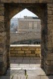 Encante la entrada en una pared de piedra antigua con vistas al panorama de la ciudad Imagen de archivo libre de regalías