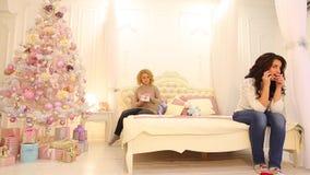 Encanto moreno y secreto de la tenencia de la muchacha del amigo, hablando reservado en celular, sentándose en cama en dormitorio metrajes