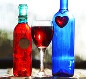 Encantos azuis vermelhos ainda da vida de vinho das garrafas de vidro & do coração & da cerâmica Imagens de Stock
