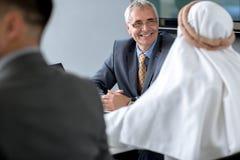 Encargado alegre de las RRPP de la compañía que habla con el hombre de negocios árabe Imágenes de archivo libres de regalías