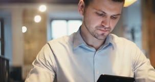Encargado cansado del doctor del abogado del oficinista del hombre de negocios que usa el suyo tableta de computadora personal en metrajes