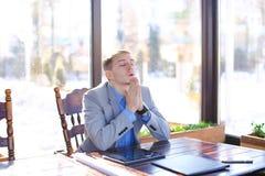 Encargado cansado joven que tiene rotura en el café con el papel de rollo, tableta Foto de archivo