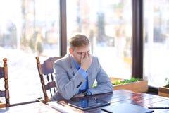 Encargado cansado joven que tiene rotura en el café con el papel de rollo, tableta Imágenes de archivo libres de regalías