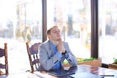 Encargado cansado joven que tiene rotura en el café con el papel de rollo, tableta Imagenes de archivo