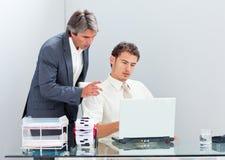Encargado concentrado que ayuda a su colega a trabajar Imágenes de archivo libres de regalías
