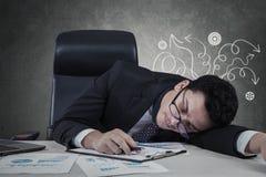 Encargado confuso que duerme en el escritorio Foto de archivo libre de regalías
