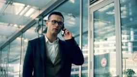 Encargado corporativo ocupado en un traje que habla en un teléfono, cierre para arriba