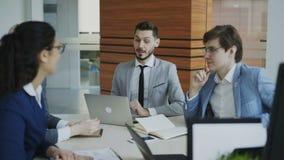 Encargado de Execuctive que discute el plan empresarial con los colegas que se sientan en la tabla en oficina moderna