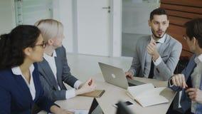 Encargado de Execuctive que discute el plan empresarial con los colegas que se sientan en la tabla en sala de reunión de la ofici