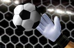 Encargado de la meta que intenta coger un balón de fútbol rápido Imagenes de archivo