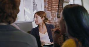 Encargado de la mujer del encargado que habla con los colegas o los empleados Grupo de gente multiétnica que tiene el equipo info almacen de video
