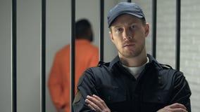 Encargado de la prisión que mira a la situación de la cámara cerca de la célula con el afroamericano encarcelado almacen de video