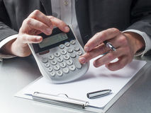 Encargado de las finanzas que cuenta con el foco en la calculadora Fotos de archivo libres de regalías